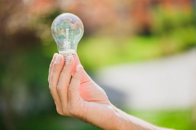 Die hand eines mannes, die transparente glühlampe gegen unscharfen hintergrund zeigt