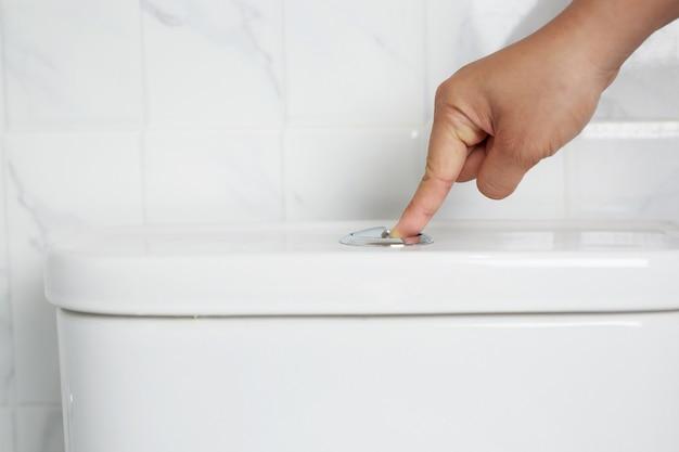 Die hand eines mannes drückt einen knopf in der toilette