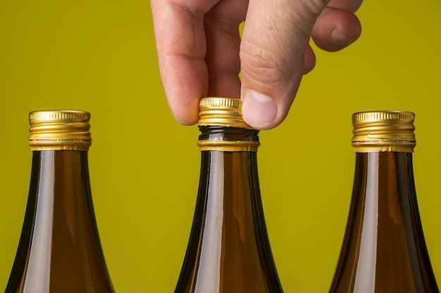 Die hand eines mannes entfernt den deckel von einer glasbierflasche