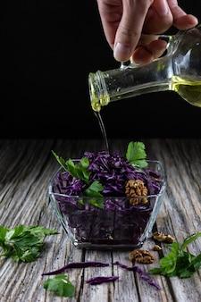 Die hand eines mannes gießt pflanzenöl über einen rotkohlsalat auf holztisch und schwarzem hintergrund