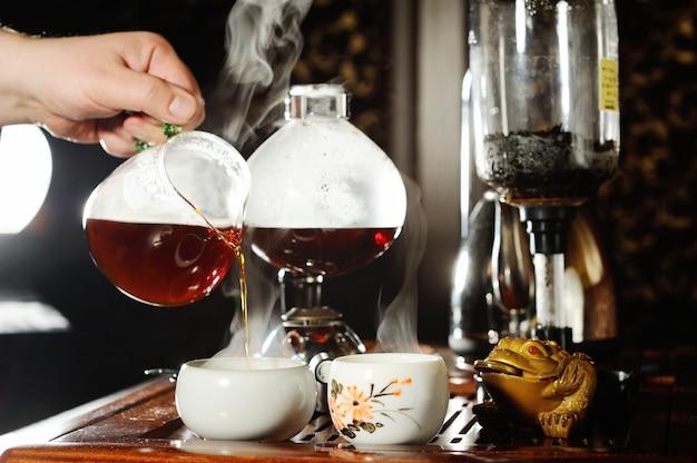 Die hand eines mannes gießt schwarzen tee in eine schöne chinesische schüssel