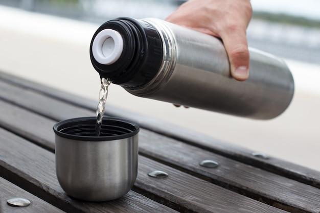 Die hand eines mannes gießt tee aus einer thermoskanne in eine tasse auf einer bank.