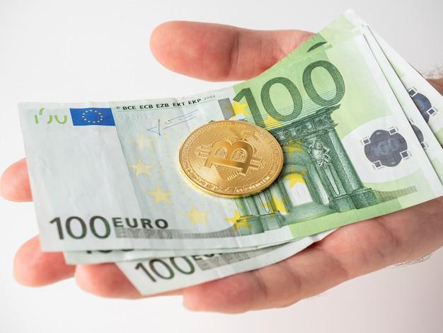 Die hand eines mannes hält 100-euro-scheine und einen goldenen bitcoin in seiner handfläche. das konzept des mining und mining von kryptowährung