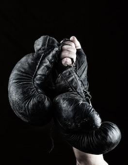 Die hand eines mannes hält ein paar alte schwarze boxhandschuhe aus leder