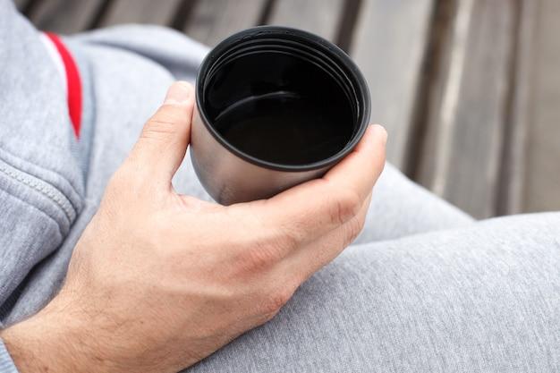 Die hand eines mannes hält eine tasse tee oder kaffee aus einer thermoskanne.
