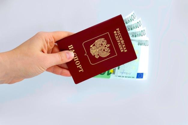 Die hand eines mannes hält einen ausländischen pass der russischen föderation mit banknoten