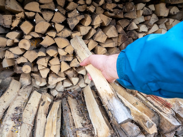 Die hand eines mannes hält einen baumstamm, der aus einem haufen brennholz gezogen wurde