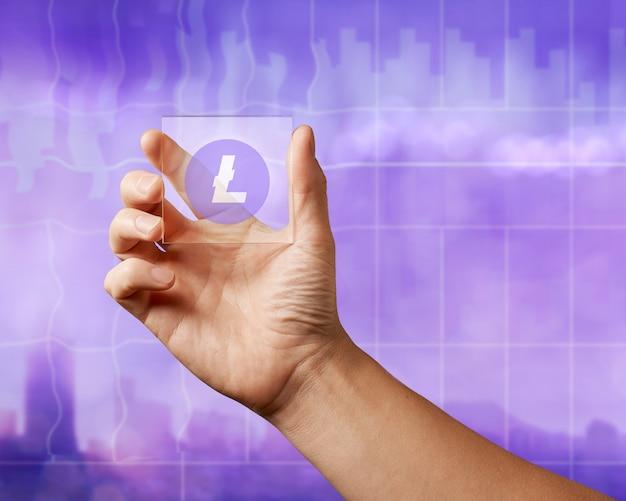 Die hand eines mannes hält einen digitalen glasbildschirm mit einem litecoin-symbol auf dem ultravioletten hintergrund der stadt. kryptowährung und blockchain-handelskonzept.