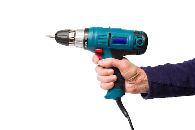 Die hand eines mannes hält einen elektrischen schraubendreher, der auf weiß isoliert ist