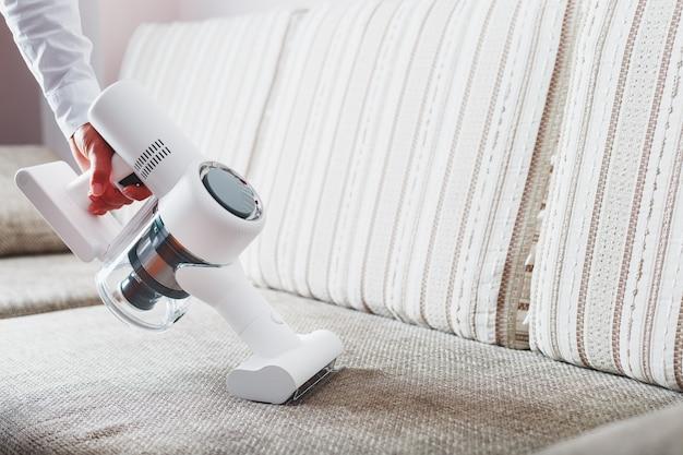 Die hand eines mannes hält einen modernen kabellosen staubsauger zum reinigen des sofas im haus.