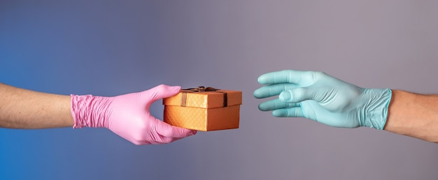 Die hand eines mannes in einem blauen handschuh gibt der hand einer frau in einem rosa handschuh eine geschenkbox