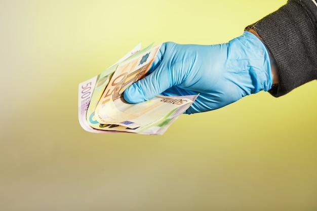 Die hand eines mannes in einem blauen medizinischen handschuh hält geld in form von euro-scheinen auf einem gelben tisch. schutz vor viren und bakterien.