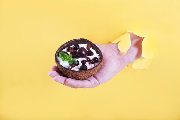 Die hand eines mannes in einem loch hält eine tasse kokosnuss mit einem dessert aus schlagsahne Premium Fotos