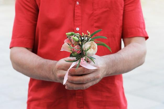 Die hand eines mannes in einem roten hemd hält einen kleinen schönen blumenstrauß