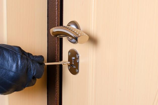 Die hand eines mannes in einem schwarzen lederhandschuh hält den schlüssel.