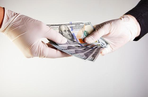 Die hand eines mannes in einem weißen medizinischen handschuh gibt einer frau in einem weißen medizinischen handschuh geld in form von hundert-dollar-scheinen. vor viren und bakterien schützen