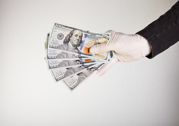 Die hand eines mannes in einem weißen medizinischen handschuh hält geld in form von hundert-dollar-scheinen. schutz vor viren und bakterien.