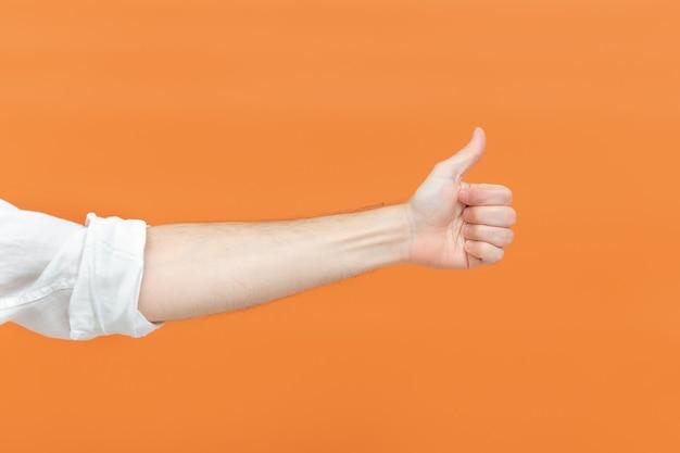 Die hand eines mannes macht ein daumen hoch zeichen auf einem orangefarbenen hintergrund. konzept der körpersprache. handzeichen. wie geste.