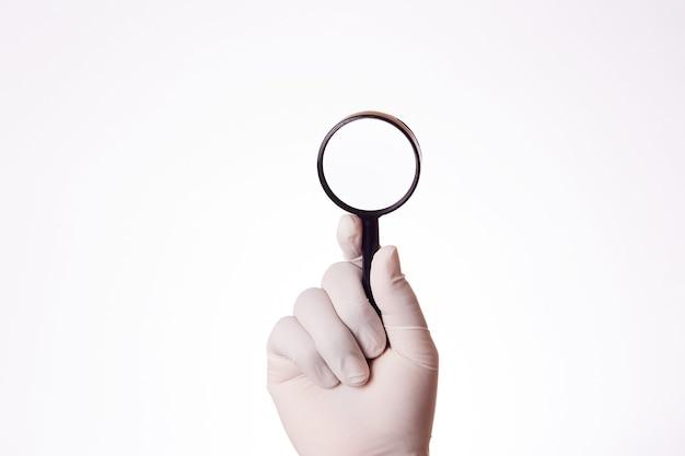 Die hand eines mannes mit einem latexhandschuh benutzt eine lupe