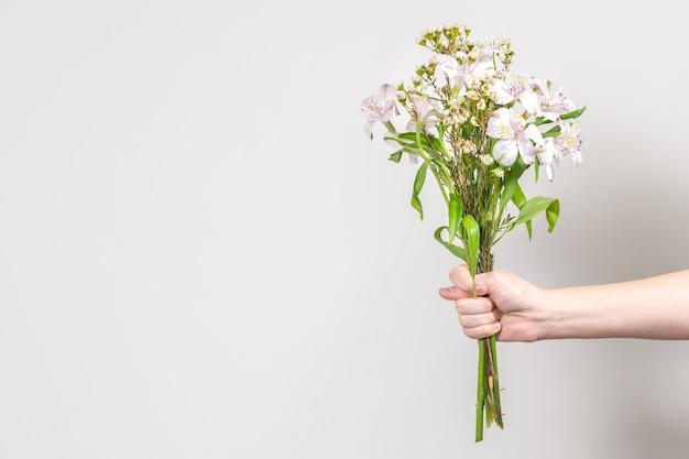 Die hand eines mannes mit einem strauß weißer blumen zeigt feigen auf einem grauen hintergrund
