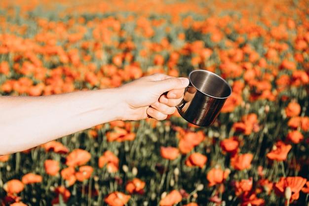 Die hand eines mannes mit einer tasse auf einem mohnfeld. positive emotionen, lebensgefühl, seelenfrieden.