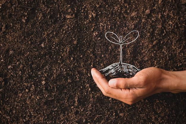 Die hand eines mannes pflanzt in seiner vorstellung einen baum, eine vorstellung von der umwelt.
