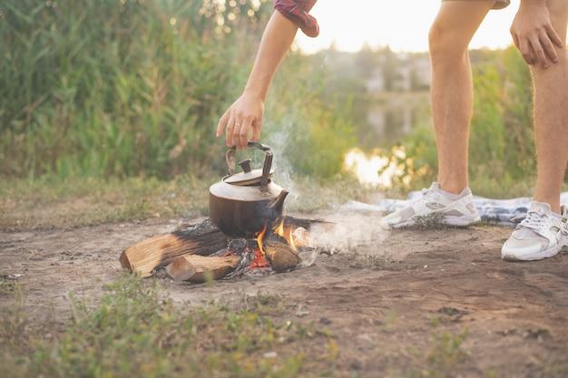 Die hand eines mannes repariert ein feuer mit einem stock, auf dem der kessel kocht