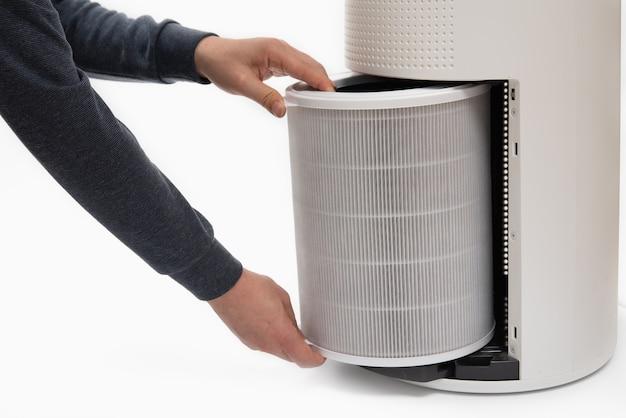 Die hand eines mannes verwandelt den filter eines luftreinigers in einen neuen.