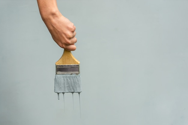 Die hand eines mechanikers mit einem pinsel malt die wand blau.