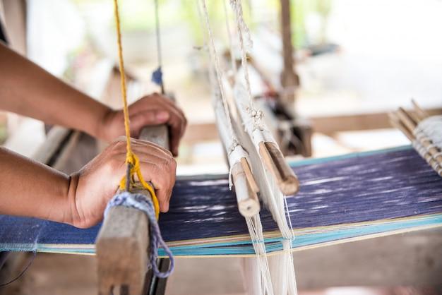 Die hand eines webers wird mit einer handgewebten maschine gewebt