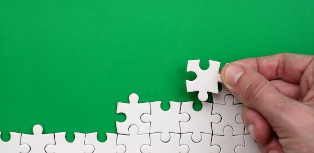 Die hand faltet ein weißes puzzle vor dem hintergrund der grünen fläche
