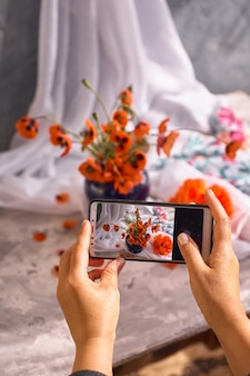 Die hand hält das telefon und fotografiert das stillleben der mohnblumen