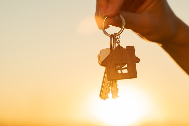 Die hand hält den schlüssel zum neuen haus mit einem schlüsselbund in form eines hauses auf dem hintergrund von ...