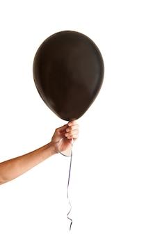 Die hand hält den schwarzen ballon der feiertag ist halloween der schwarze ballon ist für ihr logo