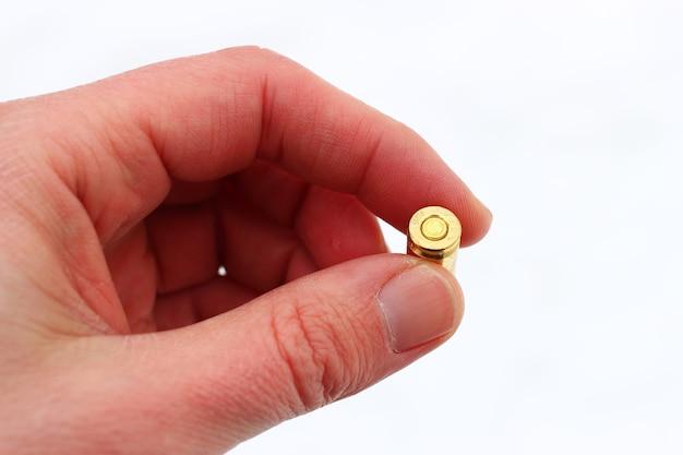 Die hand hält die pistolenpatrone auf einer weißen oberfläche