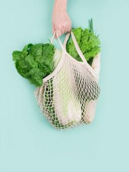 Die hand hält eine öko-tasche mit gesundem gemüse. kohl, spinatblätter, salat, zwiebel an einer minzwand. öko-shopping.