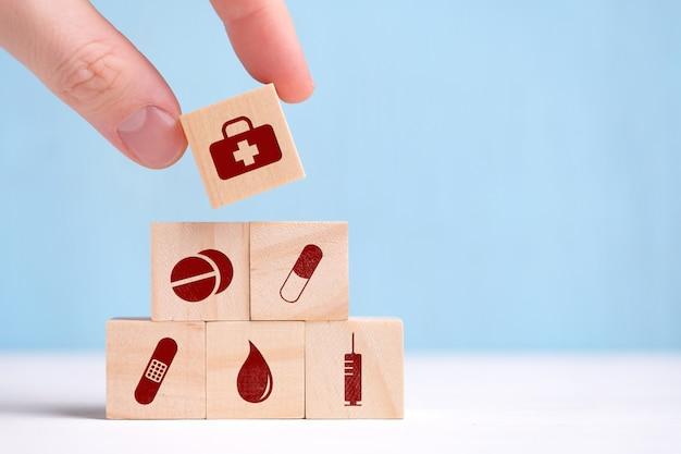 Die hand hält einen holzwürfel mit symbolen - tabletten, kapsel, pflaster, tests, spritze.