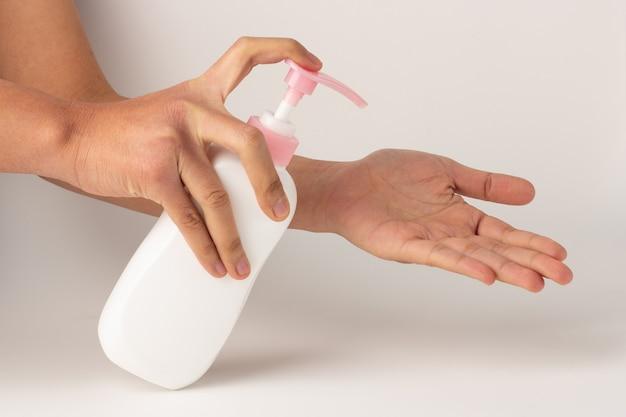 Die hand hielt die pumpflasche und drückte die lotion auf die handfläche.