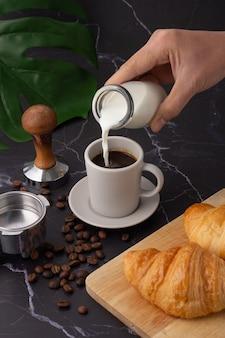 Die hand hielt eine milchflasche in einer weißen kaffeetasse, croissant auf einem schneidebrett, kaffeebohnen und eine kaffeemühle auf einem schwarzen marmorboden.