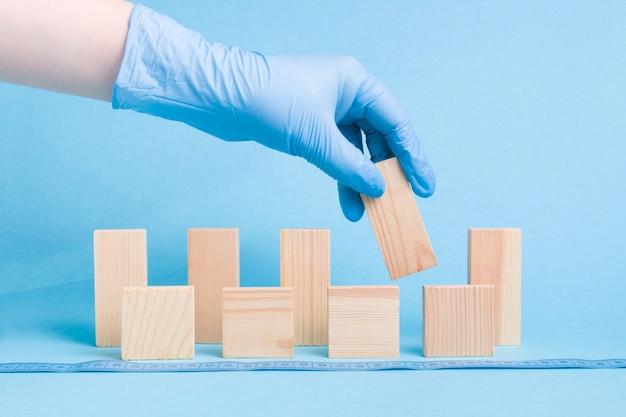 Die hand in einem blauen medizinischen einweghandschuh aus gummi nimmt einen dominoblock