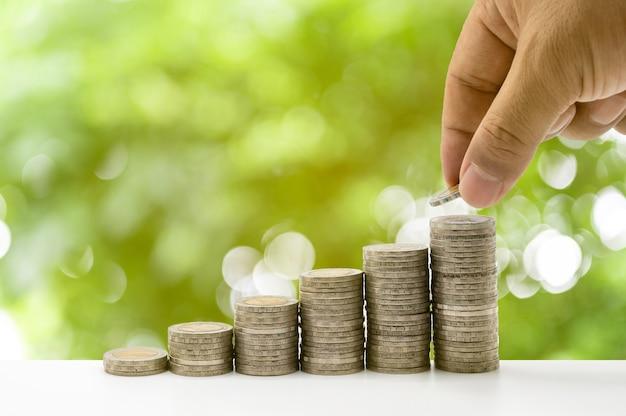 Die hand legt münzen in den stapel und münzen sammeln sich in einer spalte an, die geldspar- oder finanzplanungsideen für die wirtschaft darstellen.