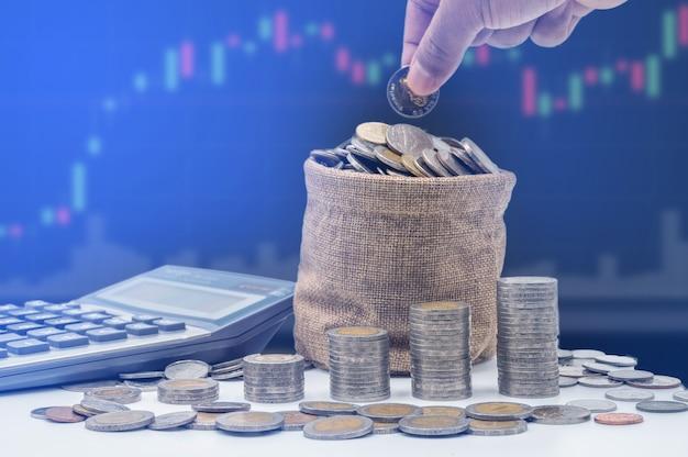 Die hand legt münzen in eine tasche und sammelt sich in einer spalte an, die geldspar- oder finanzplanungsideen für die wirtschaft darstellt.