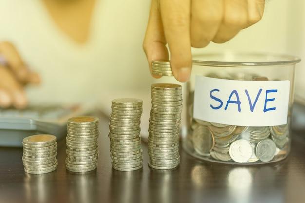 Die hand legt münzen und münzen an, die sich in einer spalte ansammeln, die geldspar- oder finanzplanungsideen für die wirtschaft darstellen.