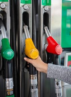 Die hand nimmt die pistole mit benzin oder diesel aus der betankungssäule