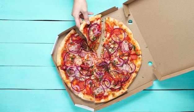 Die hand nimmt ein stück pizza in einer schachtel auf einem blauen betontisch. draufsicht