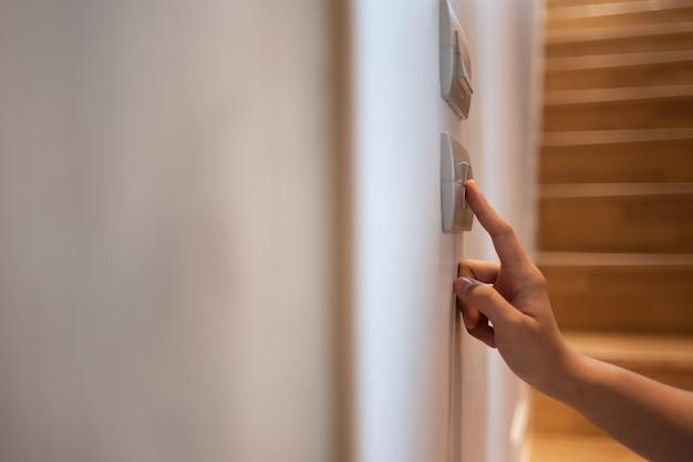 Die hand schaltet den lichtschalter aus.