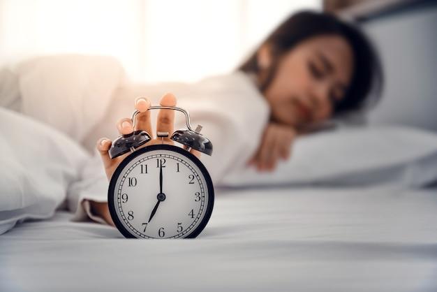 Die hand schaltet den wecker aus, der morgens aufwacht