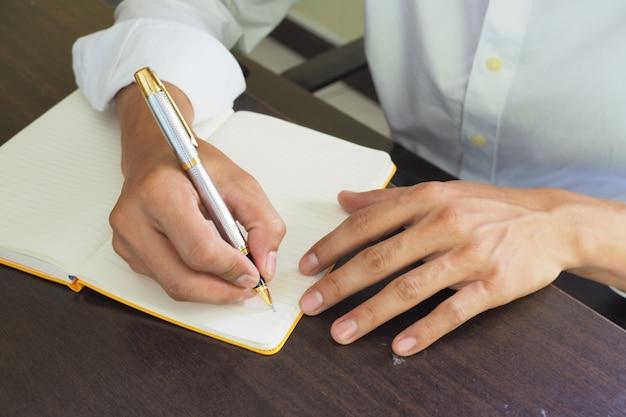 Die hand schreibt auf notizbuch