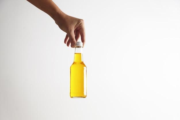 Die hand stellt die geschlossene rustikale glasflasche mit dem leckeren kalten getränk ab