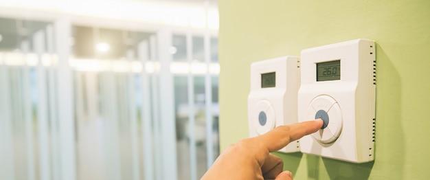 Die hand stellt die temperatur am fernbedienungsschalter des thermostats ein.